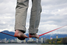 photo shows close of up a man's feet on a tightrope high above office buildings